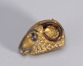 In the form of a ram's head, with attached horns that curl up and around the ears, and black, faceted, glass eyes. Small, curved metal lid located at back of head. Striker in recessed groove on bottom.