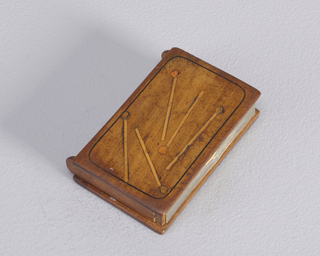 A wood rectangle matchsafe with side hinges opening the side. Depicted on the front lid are 5 matches.