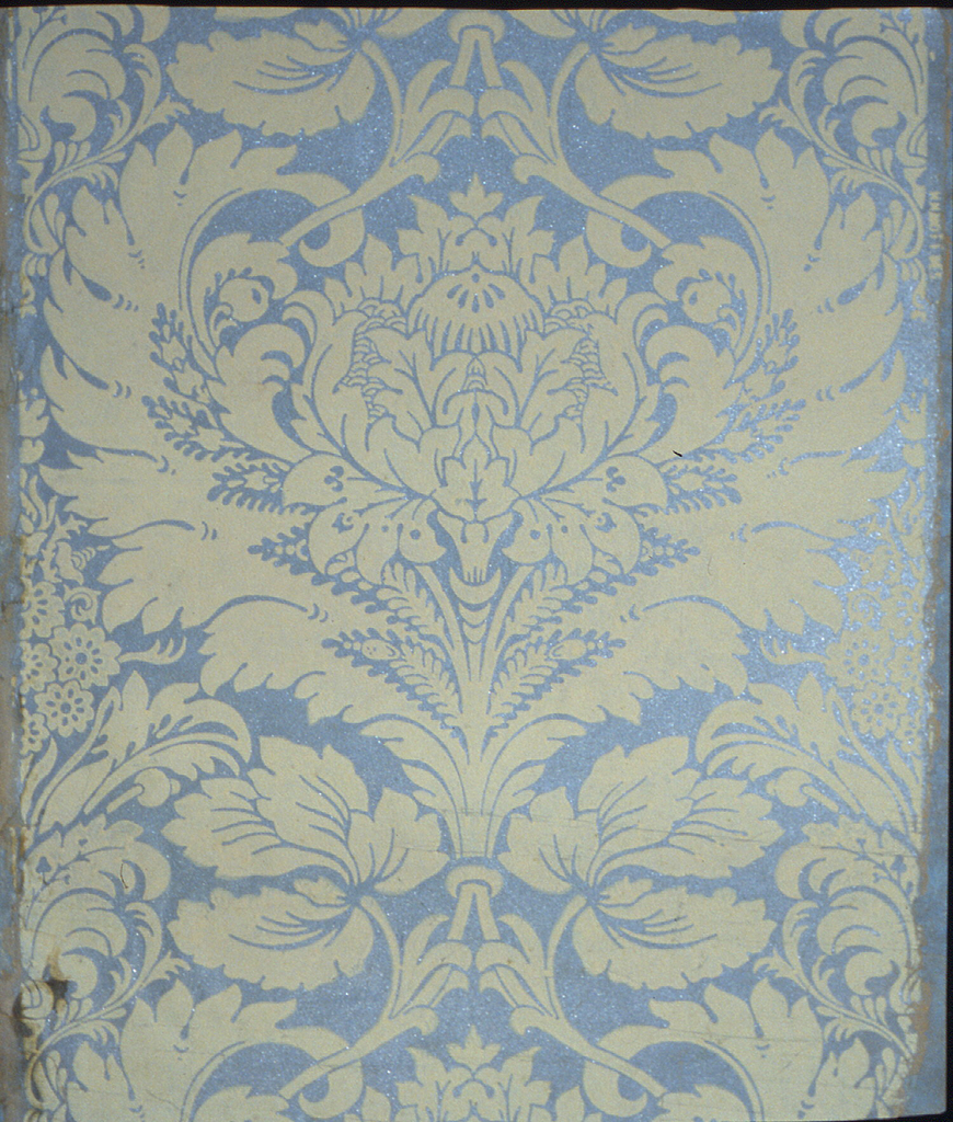 Acanthus-like frond surrounds cabbage rose outsize motif interspersed with lacy floral clusters. Design printed in cream color on light blue mica ground.