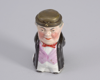 Figure of man wearing long black coat, lavender waistcoat, red tie and metal hat.