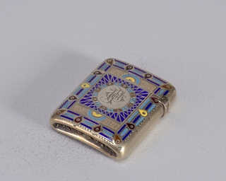 Rectangular, rounded corners, reverse slightly concave, with polychrome enamel and etched decoration, the square central reserve features open circle with monogram, the border of which is punctuated by alternating light blue and red square sections with perforations in center of each, on dark blue enamel ground an etched zig-zag design resembling sunrays radiates outwards from circle, square central reserve bordered on top and bottom by pink-beige strips with etched curly lines at each end, the center of each featuring light blue and yellow semi-circles with sawtoothed etched borders, outermost border comprised of alternating light and dark blue bands punctuated by tear drop motifs in yellow and red enamel, each of which has single perforation at their center; sides and reverse have gold wash on surface. Lid hinged on upper left side. Striker in recessed groove on bottom.