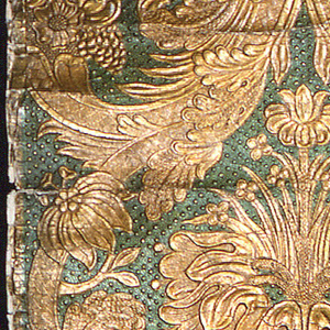 On studded-texture background, embossed symmetrical design of tulips, chrysanthemums, lilies, sunflowers and many other floral depictions, with feathery fronds of leaves; printed in metallic emerald green and metallic gold.