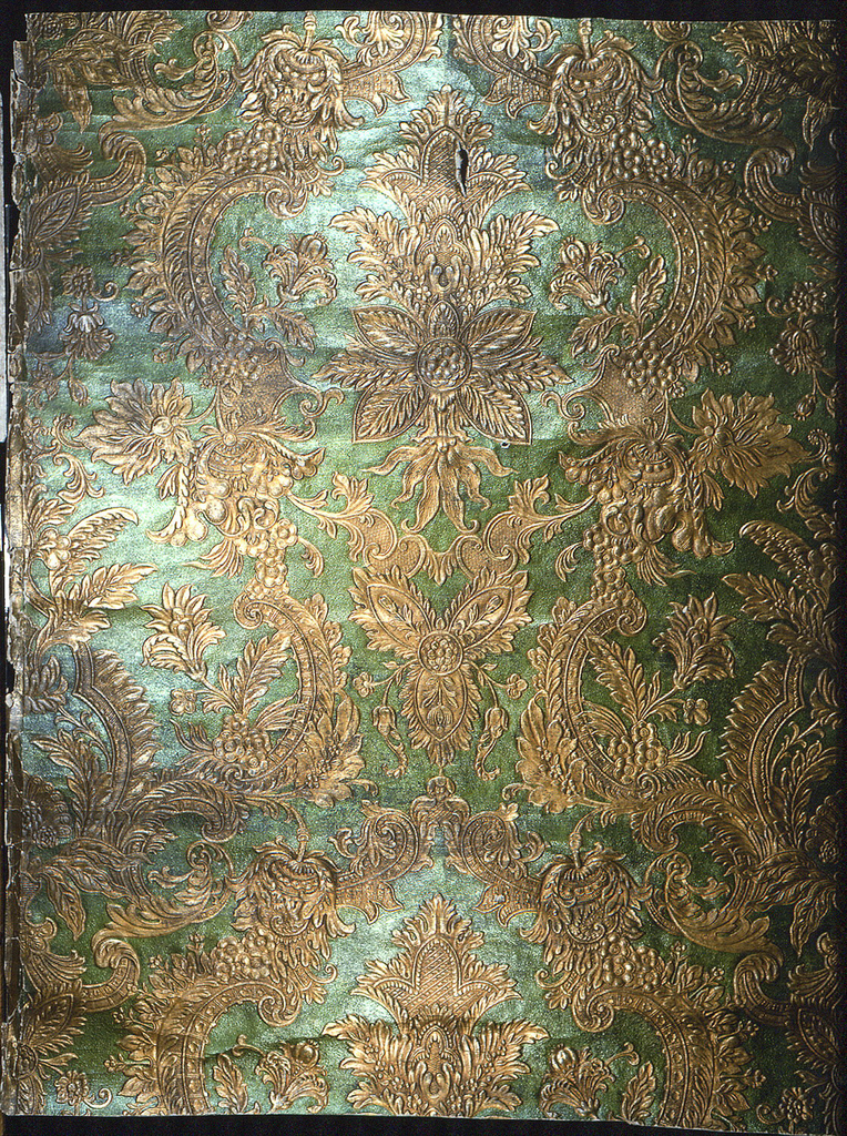 Embossed symmetrical rococo foliate and floral pattern of realistic and symbolic motifs on background of stippled texture; printed in metallic lime-green and metallic gold.