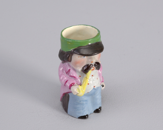 Figure of man wearing lavender coat with teal cuffs, white short pants and light blue stripes, long white waistcoat with red trim, white ruffled shirt and mustard hat. Shoe broken off base. 18th c. style ooutfit.