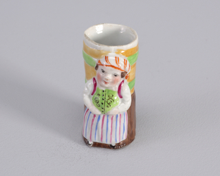 Figure of woman wearing skirt with red and blue stripes and kerchief with red stripes. Figure standing in front barrel.