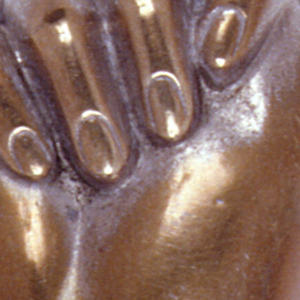 In the form of a clenched hand with ruffled cuff, thumb between index finger and middle finger. Circular lid at base, hinged on back. Striker on bottom.