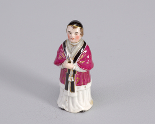 Figure of priest wearing magenta robe over gown.