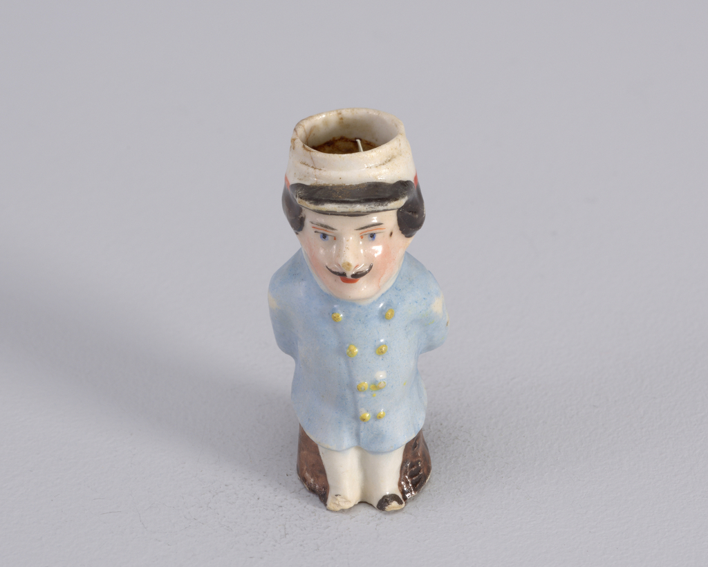 Figure of man in military outfit with white pants and light blue coat. Figure wears cap and stands with hands behid back.