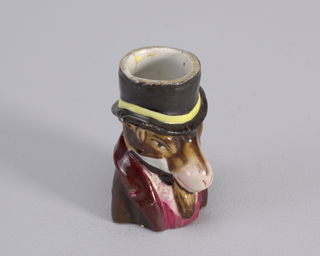 Figure of donkey wearing top hat with yellow band. Figure also wears maroon coat with magenta waistcoat and white shirt with magenta dots.