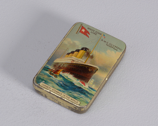 "Rectangular, curved corners, snuff box style container, cover features polychrome, printed decoration of large cruise ship on the water with mast and American flag at top, smaller sailboat in front and in background, inscribed at top ""White Star Line,"" small red banner with star to left, ""R.M.S. Olympic, 45.324 Tons"" inscribed at right, ""Largest Steamer In The World"" inscribed below. On underside ""Cadbury, Bourneville"" impressed in metal. Striker on underside."
