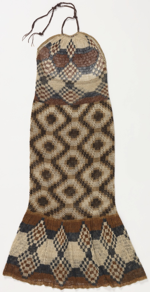 Halter-style dress with a tie at the neck and a deep flounce at the bottom. Looping is tighter in the mid-section to provide shaping.  Geometric pattern of diamond patterns in off-white, tan, dark brown and dark blue.