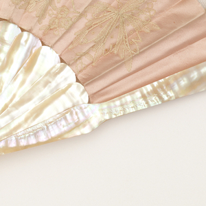 "Pleated fan, pink satin leaf with applied decoration of white lace. In the center is the monogram: ""F.S."" Sticks are plain mother-of-pearl."