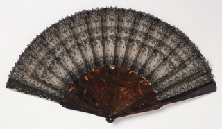 Pleated fan with leaf of black Chantilly lace on white gauze. Sticks are plain tortoise shell.