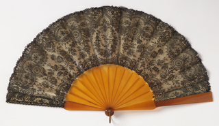 Pleated fan. Leaf of black Chantilly lace backed with linen. Lace showing wreath of roses with flowering stems within ornamental border. Sticks of amber colored celluloid.