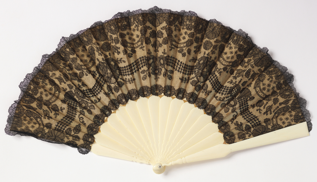 Pleated fan. Leaf of black silk lace backed with silk. Lace showing flowers and ornamental bands within floral border.