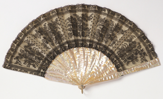 Pleated fan. Leaf of black Chantilly linen lace in design showing bunches of flowers between leaf borders. Backed with white silk. Mother-of-pearl sticks .