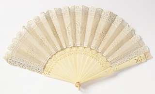 White linen leaf embroidered by machine and by hand. Design of floral palmettes and a monogram in center. Celluloid sticks and guards, carved and pierced with cartouches at the top. Cardboard case, covered and lined with silk satin