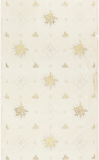 Floral sprig in metallic gold surround by gray shadow effect altnates with quatrefoil motif. Separating these elements of petite five-petaled flowers and smaller gold floral motifs. Printed on off-white ground covered with moire effect.