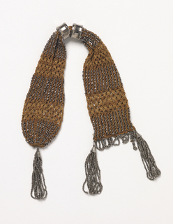 Knitted miser's purse of tan silk with cut steel beads, with beaded tassel at rounded end and bead loop fringe at flat end. Plain cut steel rings to fasten.