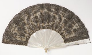 "Pleated fan. Leaf of black chantilly lace backed with stiff white georgette crêpe. Mother-of-pearl sticks. White paste jewel rivet heads. Box covered in tan silk marked ""Tiffany & Co. Union Square."""