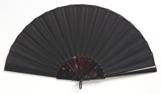 "Pleated mourning fan. Leaf of black georgette crêpe backed with organdy. Tortoise shell sticks. Black enamelled metal bail. Black satin box lined with white satin and marked ""Tiffany & Co."""