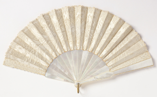 Pleated fan. Cream-colored lace leaf backed with white satin. Mother-of-pearl sticks. Yellow paste jewel at rivet. Brass bail.