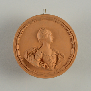 Circular form, salmon colored. Half length portrait in high relief, the shoulders to half-right, head in profile. Hair in curls. Subject wears tight-waisted robe with square decollete, corsage. Cape or scarf draped loosley about the shoulders. Wavy border. Original made at Chaumont-Sur-Loire, 1762. Copied about 1900-1910.