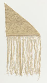 Triangular shaped ivory wool shawl fragment, densely embroidered with ivory silk in compartmentalized floral patterns. Chain stitch border with long fringe. 2/2 twill ground fabric which has been brushed, patterned by a tightly plied ivory silk yarn couched with a single ivory silk yarn. The plied silk yarn is looped as it is couched to form a linear pattern with a distinctive quality.