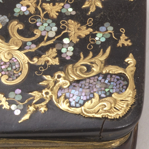 A dark blue snuff box with a decorative inlayed top depicting a winged sitting figure.