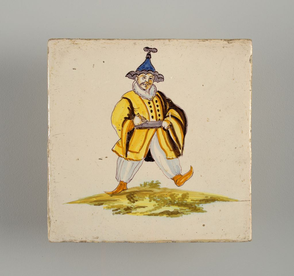 Man dressed in white trousers, yellow knee long jacket and pointed blue hat; walking to the right. Chinoiserie type decoration.