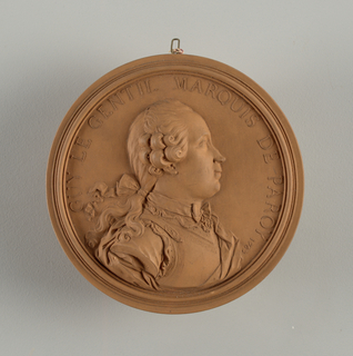 """Circular. High relief bust of young man, shoulders to half-right, head in profile. Hair dressed with ringlets and queue. wears breastplate, and cloak over shoulder. Circular border inscribed in relief: """"GUY LE GENTIL MARQUIS DE PAROY 1767""""."""