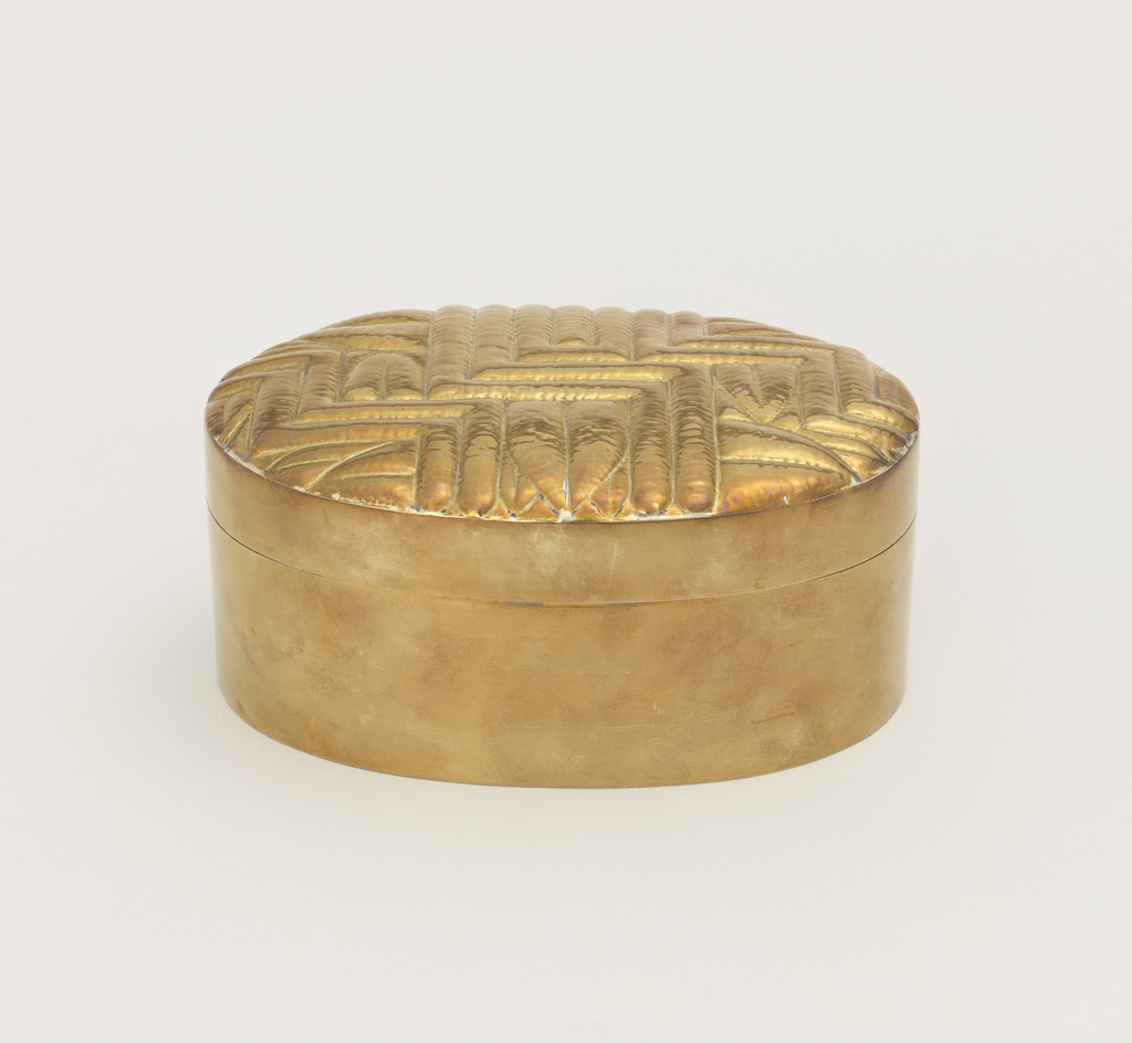 Oval, lid with repousse design of stylized leaf forms within zig-zag pattern of bands.