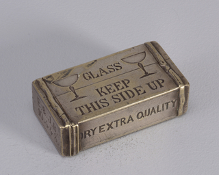 "Rectangular, in the shape of a wooden crate, featuring incised decoration of 2 champagne glasses on front, inscribed ""Glass, Keep This Side Up,"" on top, long side inscribed ""Bollinger,"" on bottom long side, inscribed ""Dry Extra Quality,"" on left side ""E. &. J. B., 10.448,"" on right side incised anchor with ""R.B. & C"" at center and larger ""P."" at lower, right-hand corner. Crate has simulated straps wrapped around each end and small incised marks resembling nail-heads on edges of sides. Lid hinged on left side. Striker on underside of box."