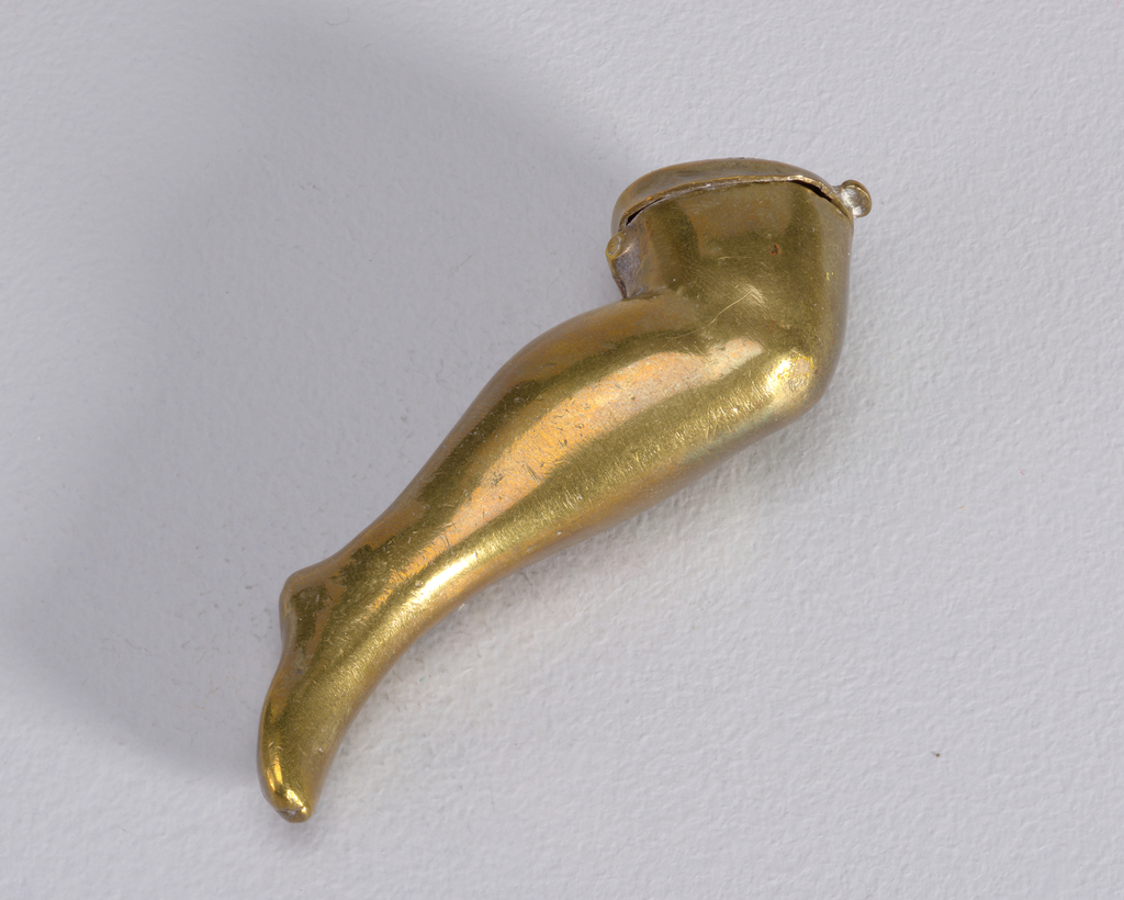 In the form of a woman's leg, from mid thigh down to the foot, knee slightly bent. Circular lid with thumb catch attached at thigh end of box, hinged on underside. Striker on top of lid.