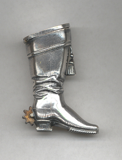 In the shape of a knee-high boot with tassle hanging from front, rotating brass spur at heel. Lid on top, hinged at back. Interior appears to have compartment for recessed pencil. Striker on sole of boot at bottom.