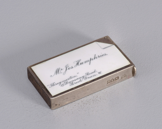 "Rectangular, featuring black and white enamel decoration, text/image reads horizontally, of a calling card with upper right-hand corner folded, inscribed ""Mr. Jos. Humphries"" at center, "" 'Throgmorton,' 19, Dunsany Road, Brook Green, W."" at lower left-hand corner. Flat lid hinged on long side. Striker on bottom."