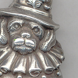"""In the shape of a seated dog with ruffled collar and feathered hat, inscribed on band on reverse side of hat """"Rd.1465""""(?- illegible impression). Lid opens at bottom, hinge on side above tail. Striker recessed in bottom."""