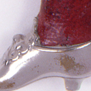 In the form of a woman's leg from knee down, with bowed, low healed shoe; red leather wrapped around curvaceous calf to simulate stocking. Oval lid at top, hinged at back, release button at front. Striker on sole of shoe.