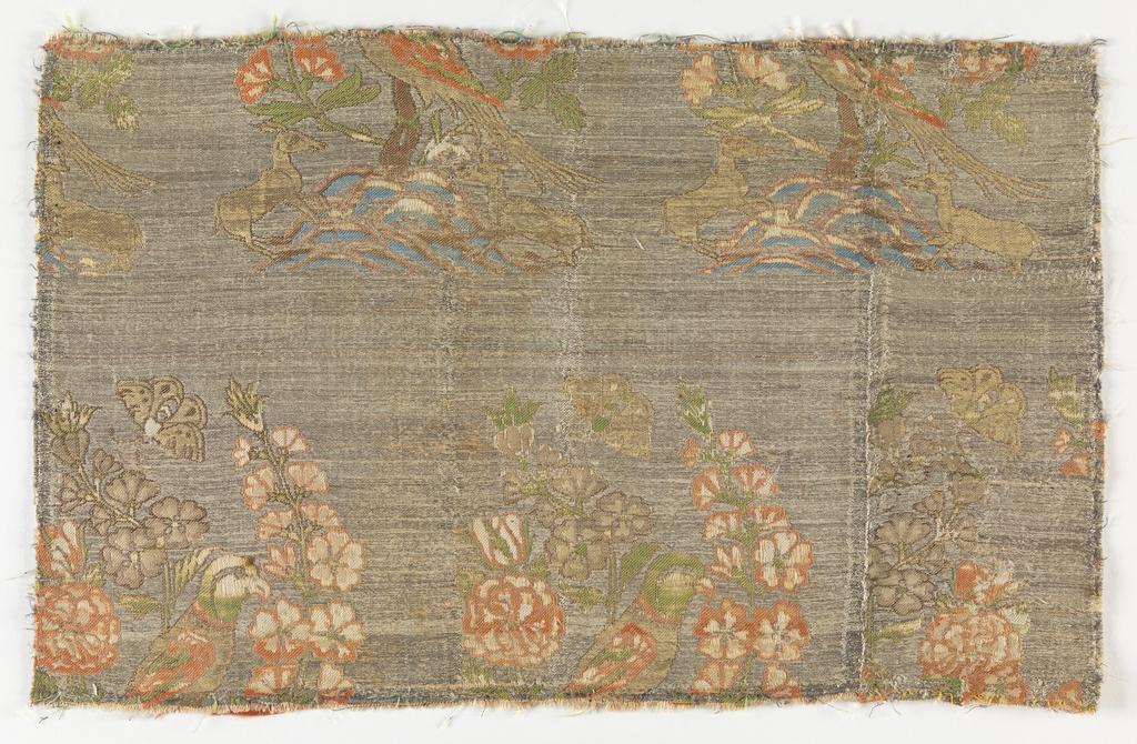 Woven silk textile fragment showing repeating pattern of deer sitting under a flowering tree with a bird and butterfly. Brown ground with discontinuous supplementary weft floats in orange, green and white.
