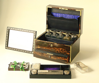 Rectangular box,lined with purple silk, fitted with leather document holders, and mirror with gold-leaf foliate border, the upper level withy 4 rectangular and 1 central faceted silver-lidded cylindrical cologne jars, 3 silver-lidded glass boxes, 2 silver-lidded glass ink bottles, mother-of-pearl handled sewing implements, tweezers, button hook, pen knife and hole punch or scorer-all in the upper compartment, a secret drawer below fitted with a letter writing slide.
