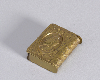 "Rectangular, in the shape of a book, featuring profile bust of King Edward VII in central, oval, and recessed reserve, surrounded by rose, thistle, clover motifs at all four corners, curved right side resembles tooled leather book spine, reverse features inscription ""Long Live The King"" and central monogram ""ER"", ground decoration of rose, thistle, clover and leaf motifs. Both top and bottom flip open, hinges on left, straight side. Striker recessed in left, straight side."
