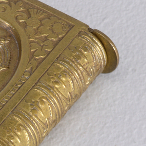 """Rectangular, in the shape of a book, featuring profile bust of King Edward VII in central, oval, and recessed reserve, surrounded by rose, thistle, clover motifs at all four corners, curved right side resembles tooled leather book spine, reverse features inscription """"Long Live The King"""" and central monogram """"ER"""", ground decoration of rose, thistle, clover and leaf motifs. Both top and bottom flip open, hinges on left, straight side. Striker recessed in left, straight side."""