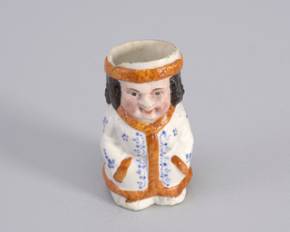 Figure of a man in white dressign gown with rust trim and blue dot pattern.