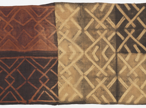 A man's ceremonial skirt which alternates two panels of red and brown and two of tan and brown, sewn together to form one long panel. All panels have interlacing patterns created through clamped resist dyeing.