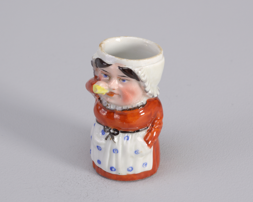 Figure of woman drinking from yellow bottle. Figure wears a rust dress with a white ruffle around the neck and a white apron with big blue dots. Figure's hand is in an apron pocket.