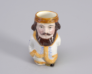 Figure of man with beard and right hand in pocket. Figure wears white dressing gown with orange trim and blue curvilinear pattern.
