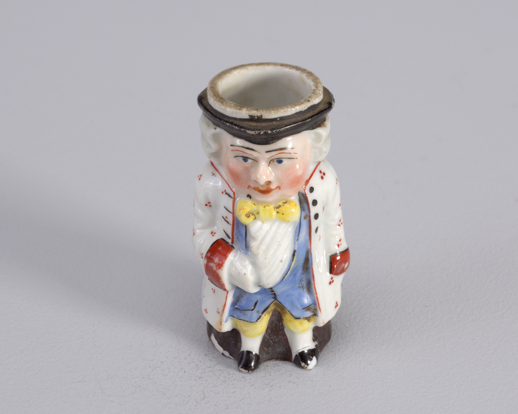 Figure of man in 18th c. costume with long white coat with red cuffs and red design, yellow short pants, long blue waistcoat, white ruffled shirt and yellow tie.