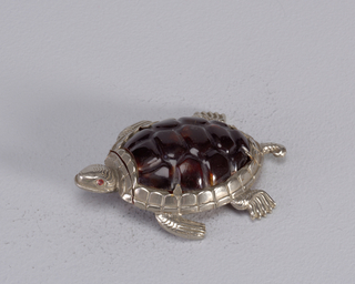 In the form of a turtle with head, legs and tail extended, its back molded from tortoise-shell colored celluloid, eyes enameled red. Head (lid) flips backwards at uppermost part of shell, hinged on underside. Ridges of underside serve as striker.