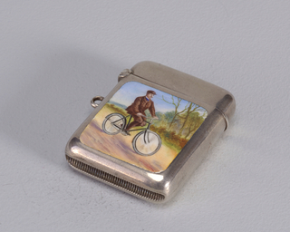 Rectangular, with rounded corners, featuring enamel reserve with male, brown moustached bicyclist in brown suit and cap, riding down country road on black bicycle, set against a wooded background and light blue sky. Lid hinged on left. Link attatched to left side. Striker recessed in bottom.
