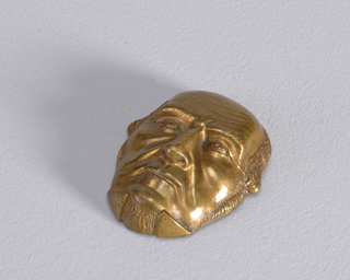 In the shape of British Prime Minister Gladstone's face, reverse undecorated and flat. Box opens on reverse, horizontal hinge near center. Striker in recessed groove on reverse.